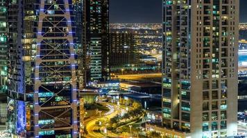 Buildings of Jumeirah Lakes Towers with traffic on the road night timelapse