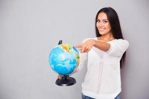 Woman pointing finger at globe