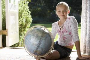 Girl (8-10) sitting with globe by French doors, smiling, portrai