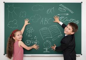 school boy and girl draw on board