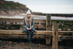menina sentada na defesa do mar