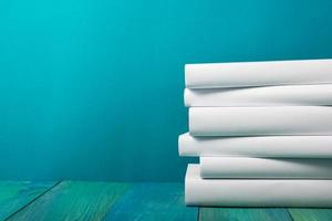Stack of white books, grungy blue background, free copy space