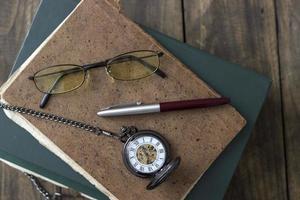 um relógio de bolso antigo, óculos e livros