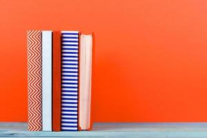 Row of colorful hardback books, open book on red background