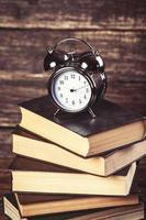 Alarm clock and books on wooden table. photo