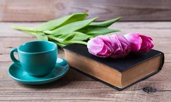 Cup of coffee on book with flowers.