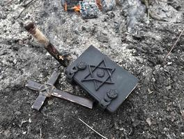 Wooden cross, stake and black magic book on the ashes photo