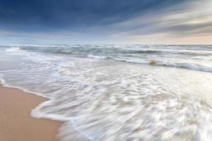 Olas del mar del norte en la playa de arena foto