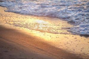 Sea wave on sandy beach photo