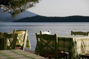 Mesas de café cerca del mar con árbol.