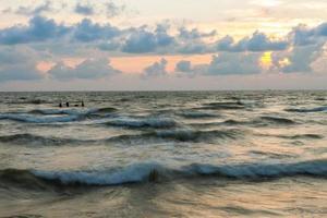 Olas del Báltico con muelle destruido al atardecer foto