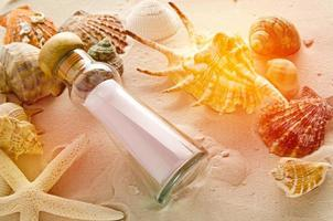 bottle letter and sea shells on sand background photo