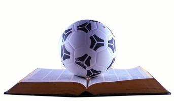 balón de fútbol sobre libro