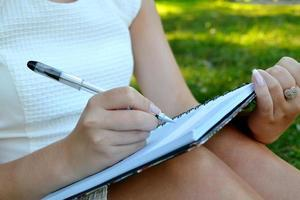 Woman with beautiful hands writing in her diary