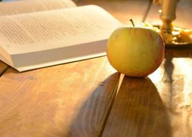 Warm scene with open book and apple photo