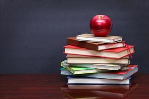 Stapel Bücher und roter Apfel auf dem Schreibtisch