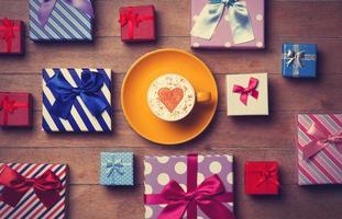 Taza y cajas de regalo sobre fondo de madera
