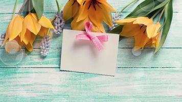 Fondo con tulipanes frescos, muscaries y etiqueta vacía.