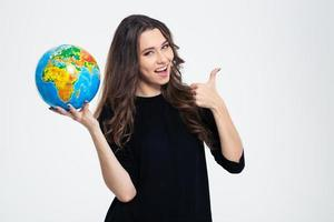 Happy woman holding globe and showing thumb up