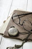 Pocket watch, glasses and old notebook on table photo