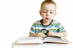 child reading a book with a magnifying glass
