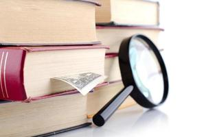 Old books with a loupe on white background Isolated