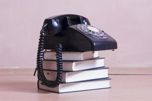 stack of books with vintage telephone on top
