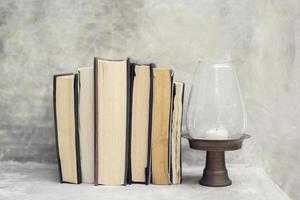 pila de libros en el estante y cerca de la lámpara.