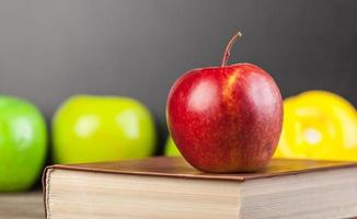 Red apple and book on a table. photo