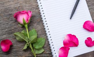 rose flower and notebook on table