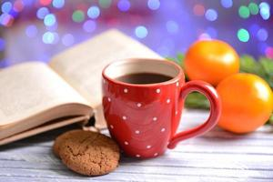 Composition of book with cup of coffee and Christmas decorations