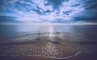 Sea wave on the beach at sunset time photo