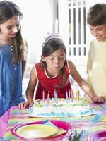 Girl Blowing Birthday Candles At Party