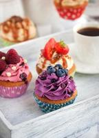Different delicious cupcakes and coffee cup photo