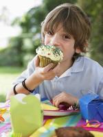 Young Boy Eating Cupcake At Birthday Party