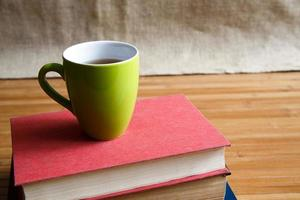 Cup of coffee on old books photo