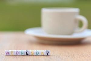Domingo escrito en cuentas de letras y una taza de café.