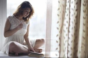 Pregnant girl sitting on the windowsill