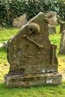 teschio e ossa incrociate tomba di pietra