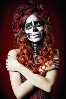 droevige jonge vrouw met muertosmake-up (suikerschedel)