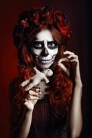 Young woman with muertos makeup (sugar skull) piercing voodoo doll