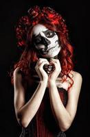 Mujer joven con maquillaje de calavera (calavera de azúcar) haciendo signo de corazón