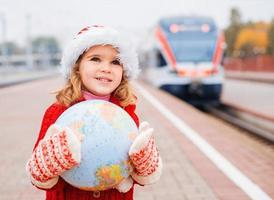 Little girl Santa travelling with a globe