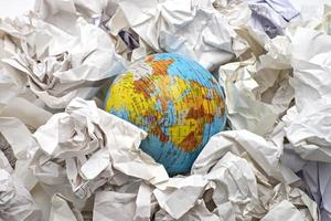 Globe among crumpled papers, view from above