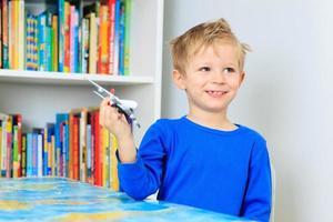 kleine jongen speelt met speelgoed vliegtuig vliegt over wereldkaart