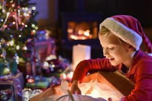 época de natal, garotinho abrindo um presente perto de uma árvore