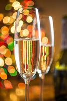 two glasses with champagne against sparkling Christmas tree