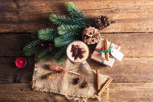 Cocoa on a wooden table with Christmas decorations, branches, spices