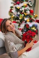 mujer sonriente con flor sentada cerca del árbol de navidad