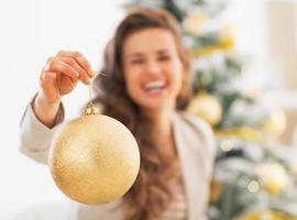 Primer plano de la bola de Navidad en la mano de la joven feliz